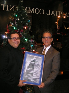 Curator and Professor Pedro Valentin presents CCC President Wilfredo Nieves with an exhibit poster.